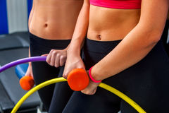 Bare female belly with dumbbells and hoop at gym. royalty free stock photography