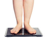 Bare female feet standing on bathroom scale Royalty Free Stock Image