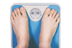 Bare female feet standing on bathroom scale stock images