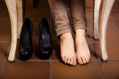 Bare female feet under the vintage table. Royalty Free Stock Photography