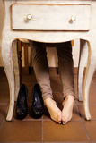 Bare female feet under the vintage table. Royalty Free Stock Photos