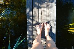 Bare female feet on a wooden bridge . the view from the top Royalty Free Stock Photography