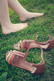 Bare female legs on grass near stand sandals. tinted Royalty Free Stock Image