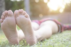 Bare foot of Asain women lying on the green grass for relaxing in the park city with bokeh of light. Background Stock Photos