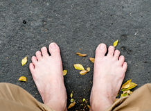 Bare foot on black stone and dried leaves Stock Image