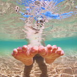 Bare foot child on beach vacation. Underwater photo stock photography
