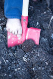 Bare foot of a little child digging with a spade Royalty Free Stock Photos