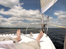 Bare foot of a man who is lying on the deck of the yacht. Blue sky, white clouds and sail Stock Photo