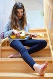 Teen girl playing ukulele guitar royalty free stock photos