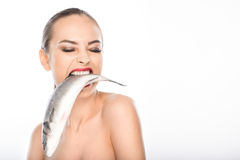 Bare girl biting seafood with desire. Wild naked woman is holding fish in mouth with hunger. Isolated and copy space in right side Stock Photography