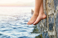 Bare girl`s feet dangling from the stone jetty royalty free stock image
