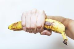 Bare hand holding banana. Royalty Free Stock Photo
