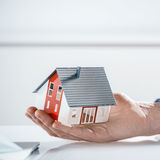 Bare Hand Holding Miniature Architectural House Stock Photo
