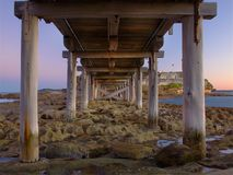 Bare island bridge. A wooden bridge leading to an island taken underneath the bridge. Sun has set Royalty Free Stock Images