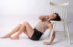 Bare Leg Beauty. An image of a gorgeous young woman with thin bare legs leaning on a chair Stock Photography