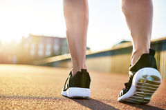 Bare legs in running shoes preparing to exercise. On a bright summer day on an empty road Stock Photos
