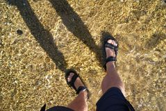 Bare legs with sandal feet standing in low tide beach. royalty free stock photo