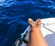 Bare legs of woman on boat. Bare tanned legs of woman on boat during trip. Dark blue sea Royalty Free Stock Photography