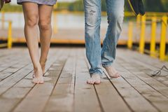 Bare male and female feet are on the footbridge of the lake pier. Walk barefoot in nature male and female Stock Photo