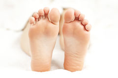 Bare relaxed feet. Soles of soft female bare feet in closeup royalty free stock image