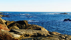 Bare rock on the coast, rough sea Royalty Free Stock Images
