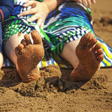 Bare sandy feet at the beach. Royalty Free Stock Image