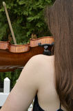 Bare shoulder violin. Teen girl playing violin seen from benind with long hair and bare shoulder Royalty Free Stock Photography