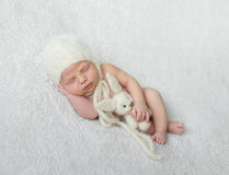 Bare sleeping baby in hat with toy on white blanket. Bare sleeping baby in hat with toy on white soft blanket with hand under his head Royalty Free Stock Photo