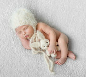Bare sleeping baby in hat with toy on white blanket Royalty Free Stock Photography