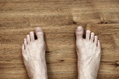 Man Feet on Parquet. Bare and somewhat hairy feet of an adult caucasian man, on brown parquet floor. Viewed from directly above Stock Image