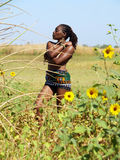 Bare top black woman outdoors green grass. Topless black woman outdoors green grass yellow flowers blue sky Stock Photography