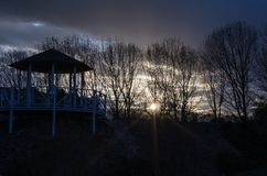 Bare tree branches and garden house against the sunset. Dark evening stock photography