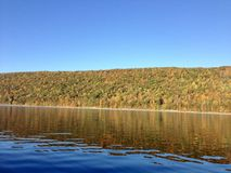 Canadice Lake, one of New York`s Finger Lakes. Bare trees on the shore of the clear, still water of Canadice Lake, one of Finger Lakes in New York, in horizontal stock images