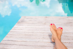 Bare woman feet by the swimming pool Royalty Free Stock Photo