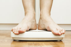 Feet on scale. Bare woman feet on a white weighting scale Stock Photography