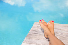 Bare woman feet on wooden deck by the swimming pool Stock Photography