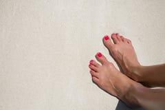 Bare woman's feet on the beach sand Stock Photos