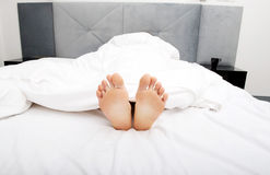Bare woman's feet in bedroom. Stock Photo
