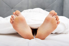 Bare woman's feet in bedroom. Stock Photos