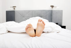 Bare woman's feet in bedroom. Royalty Free Stock Photo