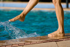 Bare women legs by the pool. A woman's is standing by the edge of a swimming pool and kicking into the water stock image