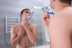 Bare young man shaving his chest and looking at the mirror. In the modern tiled bathroom at home stock photos