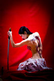 Bareback Geisha. A woman dressed like a Giesha with a dragon tattoo on her bare back and a Katana sword in her hand Stock Images