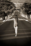 Barefeet balancing woman. Young barefeet woman balancing in the middle of the road Royalty Free Stock Photo