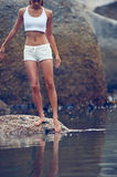 Barefeet beauty. Woman on roack at beach dipping toes in water, having fun outdoor lifestyle Stock Photography