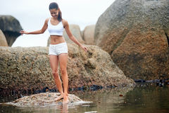Barefeet beauty. Woman on roack at beach dipping toes in water, having fun outdoor lifestyle Royalty Free Stock Photos