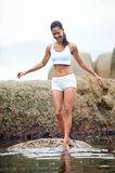 Barefeet beauty. Woman on roack at beach dipping toes in water, having fun outdoor lifestyle Royalty Free Stock Images