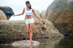 Barefeet beauty. Woman on roack at beach dipping toes in water, having fun outdoor lifestyle Stock Photo