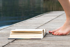 Barefeet de jeune fille sur un pilier en bois après un livre Photos libres de droits