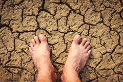 Barefeet on dry soil. Naked human barefeet on dry soil Royalty Free Stock Images